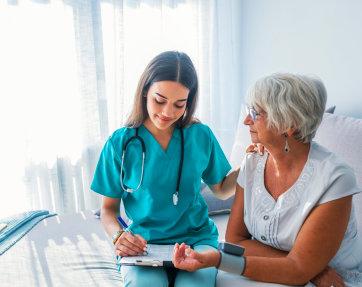 nurse takes bp test on elder woman