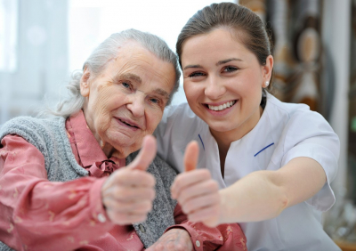 senior woman and and her caregiver giving thumbs up
