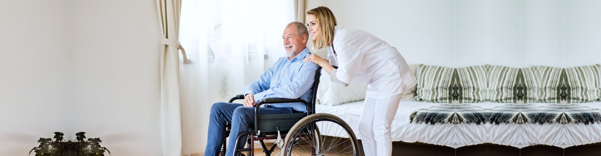 Health visitor or a nurse and a senior men in a wheelchair during home visit.